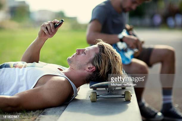 Young man resting on skateboard using mobile phone