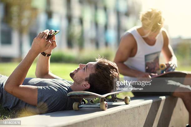 Young man resting on skateboard using phone