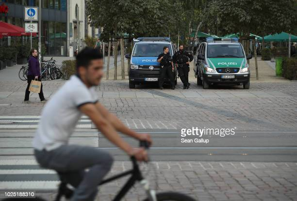 A young man rides a bicycle past police in the city center on August 29 2018 in Chemnitz Germany According to a police spokesman police have deployed...
