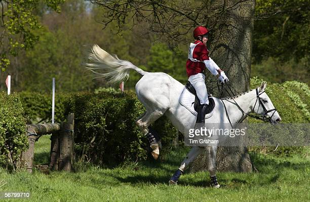 Young man rides a grey mare horse in a crosscountry eventing competition Oxfordshire United Kingdom