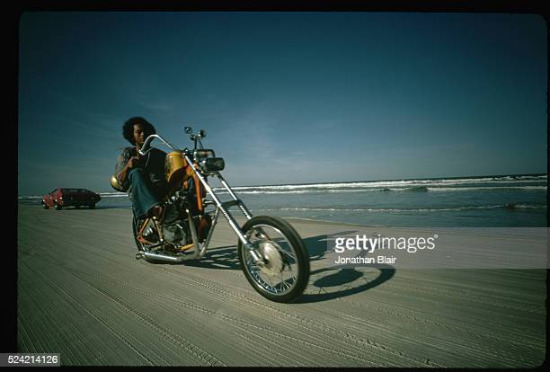 A young man rides his chopper bike near the water's edge on Daytona Beach