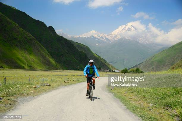 young man riding a bicycle on a scenic mountain road in a sunny summer day.snowcapped mount kazbek in the background ( 5054m altitude ) situated in caucasus mountain - tbilisi bildbanksfoton och bilder