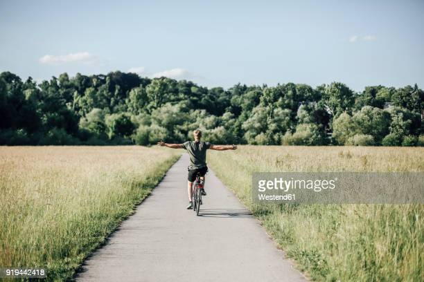 young man riding a bike, freehand - freedom stock pictures, royalty-free photos & images