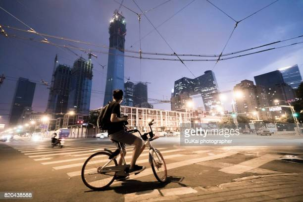 young man riding a bike on beijing cbd - beijing province stock photos and pictures