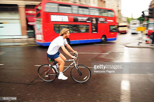 Young man riding a black bycicle in the morning close to Trafalgar Square in London, England, United Kingdom. The man, at the foreground, is wearing...