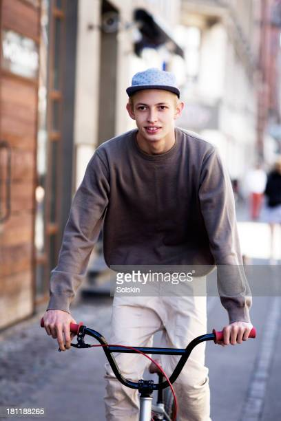 young man riding a BMX bicycle in city area