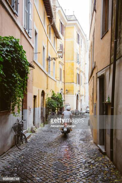 young man riding a scooter in narrow cobbled street in trastevere rome - rome stock pictures, royalty-free photos & images