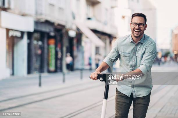 young man riding an e-scooter - motor scooter stock pictures, royalty-free photos & images