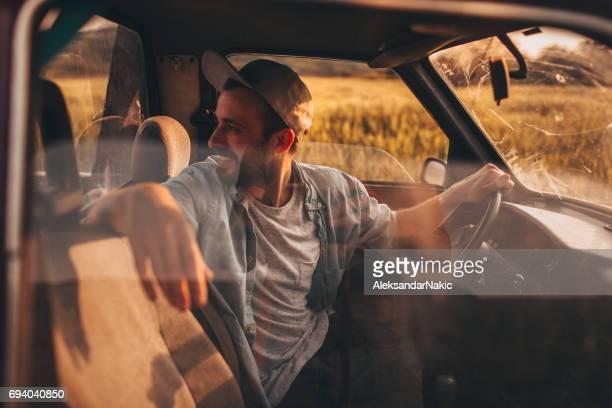 古いピックアップ トラックに乗って若い男