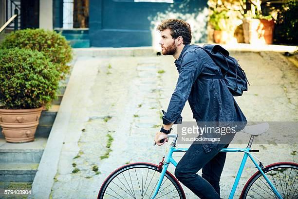 Jeune homme équitation un vélo dans la ville