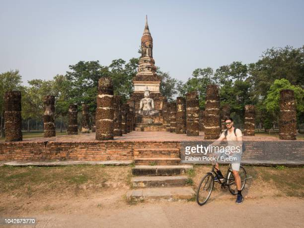 young man riding bicycle in front of ruins of sukhothai historical park, thailand - sukhothai stockfoto's en -beelden