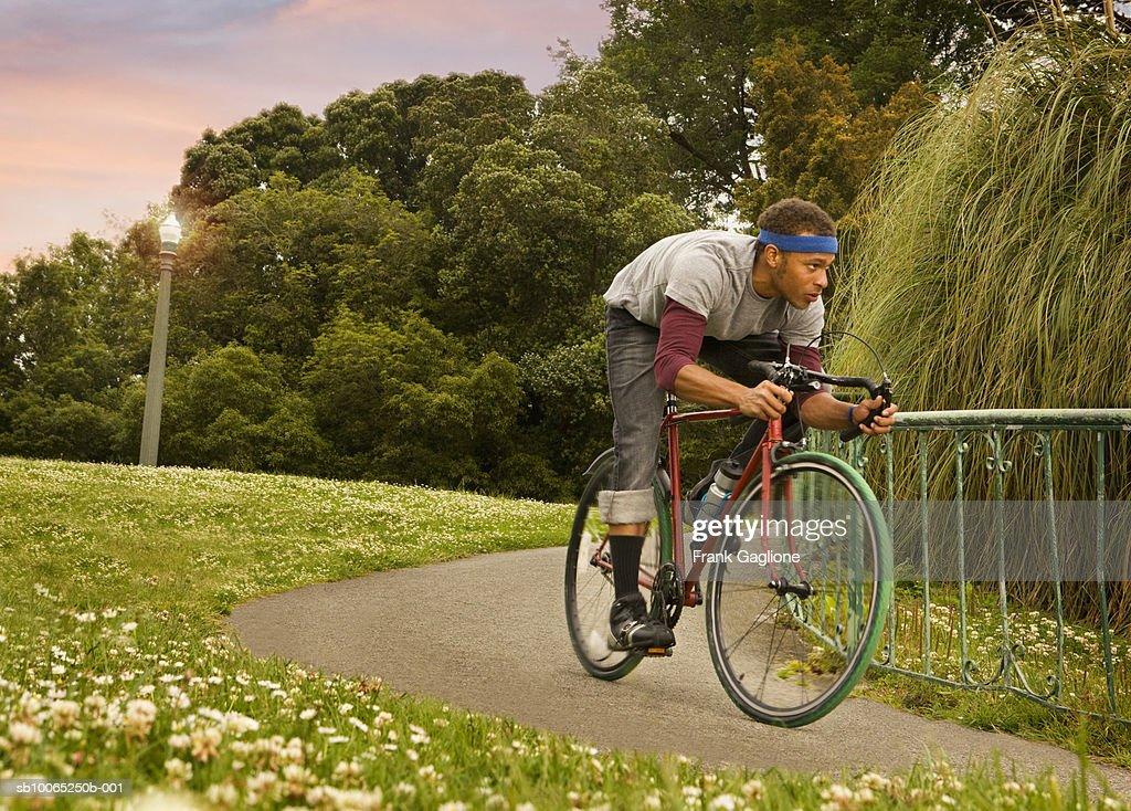 Young man riding bicycle on bike path in park : Foto stock