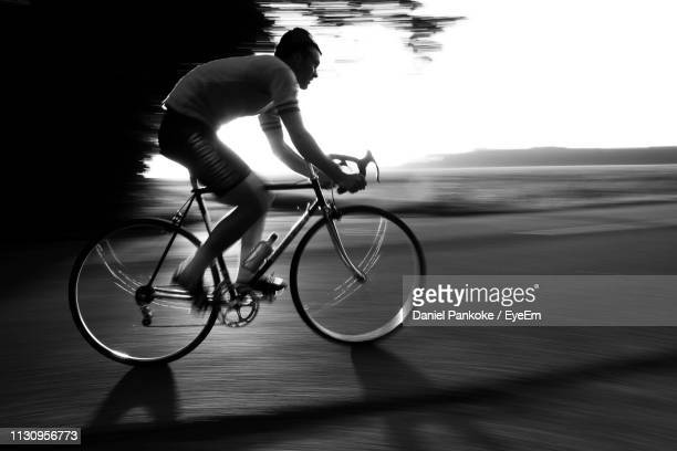 young man riding bicycle on road - forward athlete stock pictures, royalty-free photos & images