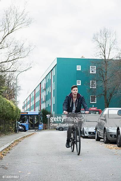 young man riding bicycle on the street, munich, bavaria, germany - movendo um veículo - fotografias e filmes do acervo