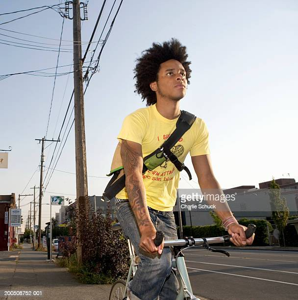 Young man riding bicycle on urban sidewalk