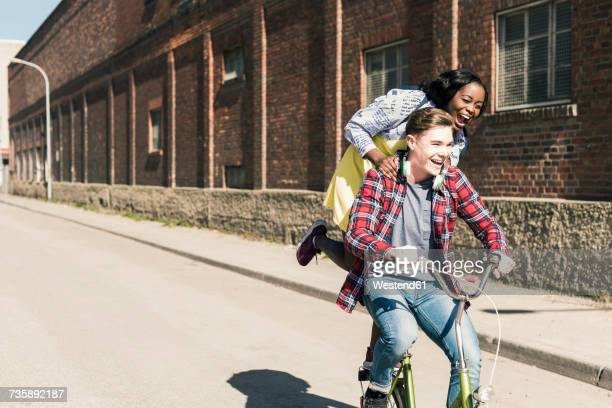young man riding bicycle with his girlfriend standing on rack - velo humour photos et images de collection