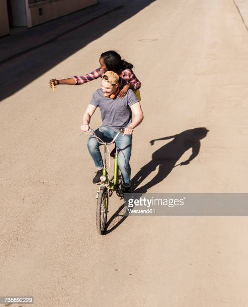 Young man riding bicycle with his girlfriend standing on rack, taking selfies