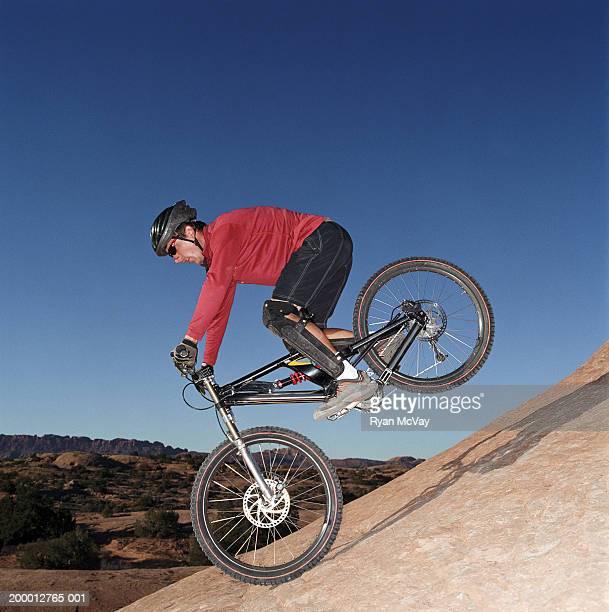 young man riding bike down mountain, side view - movimiento hacia abajo fotografías e imágenes de stock