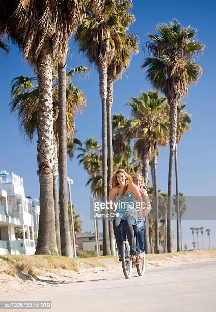 Young man riding bike with young woman on handlebars