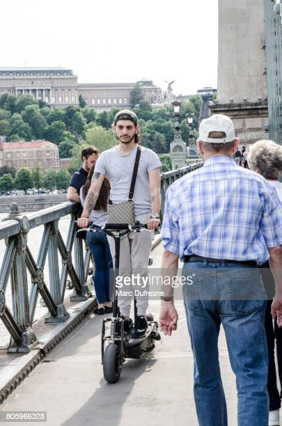 young man riding electric scooter on szechenyi bridge in budapest during summer day - mobility scooter stock photos and pictures