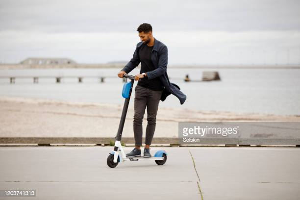 young man riding electric scooter - electric scooter stock pictures, royalty-free photos & images
