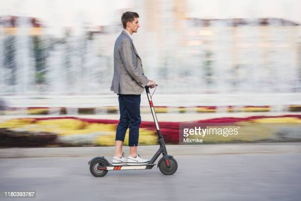 young man riding e-scooter in the city - electric scooter stock pictures, royalty-free photos & images