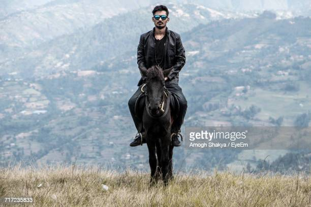 Young Man Riding Horse On Grassy Field Against Mountain