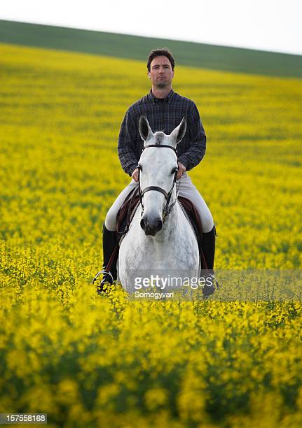 Young man riding in canola