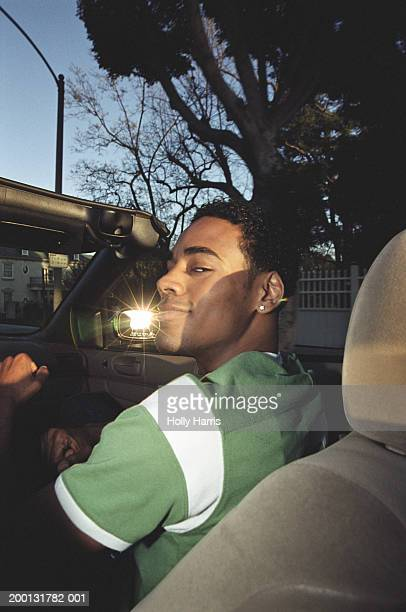 young man riding in convertible car - pimped car stock photos and pictures