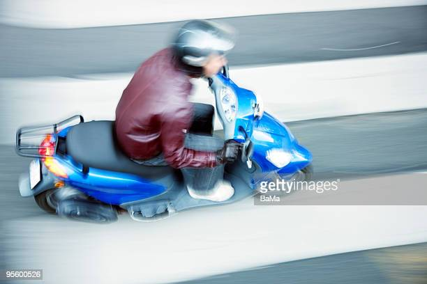 young man riding moped on zebra crosswalk - moped stock photos and pictures