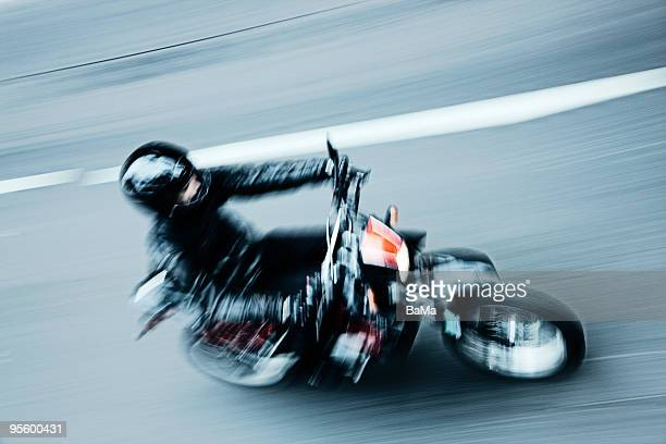 Young man riding motorcycle, blurred motion