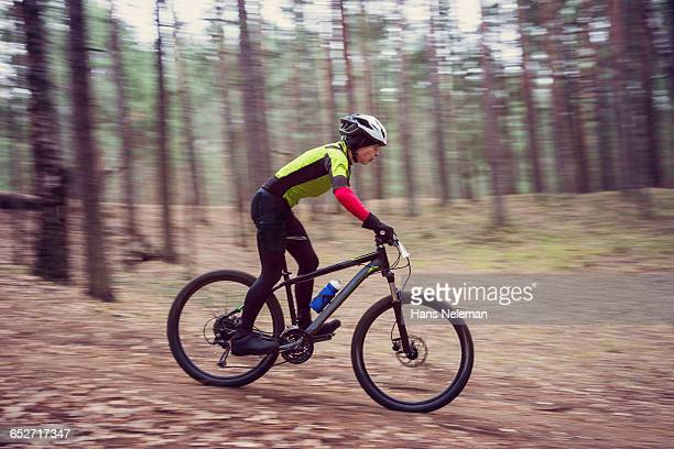 young man riding mountain bike in forest - hans neleman ストックフォトと画像