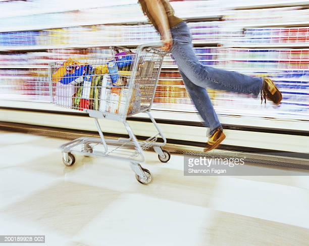 Young man riding shopping cart in supermarket (blurred motion)