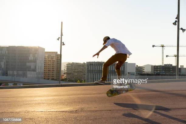 young man riding skateboard in the city - patinar fotografías e imágenes de stock