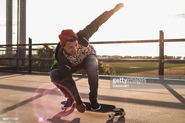 young man riding skateboard on parking level - skateboard ストックフォトと画像