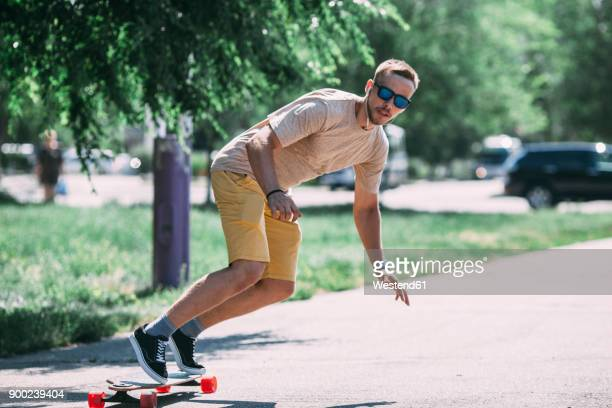 young man riding skateboard on the street - longboard skating stock pictures, royalty-free photos & images