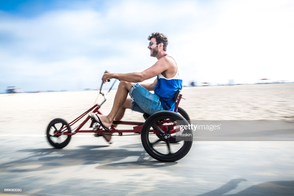 Young man riding three wheel bicycle in LA : Stock Photo