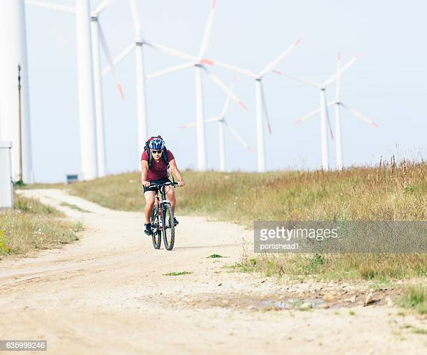 Young man riding through field with wind turbines