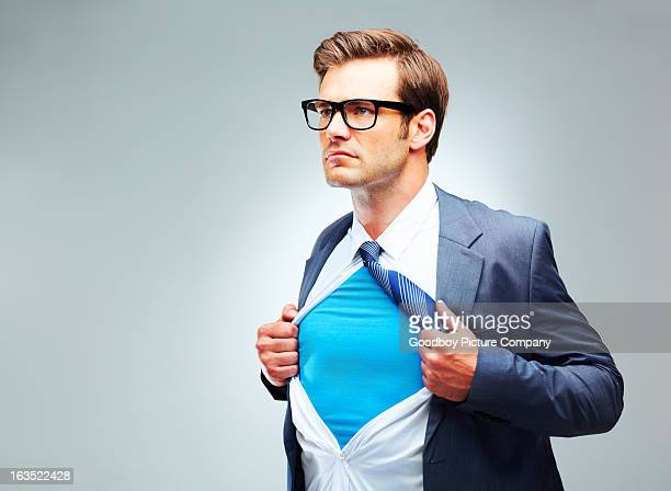 young man ripping shirt open to reveal costume - superhero stock pictures, royalty-free photos & images