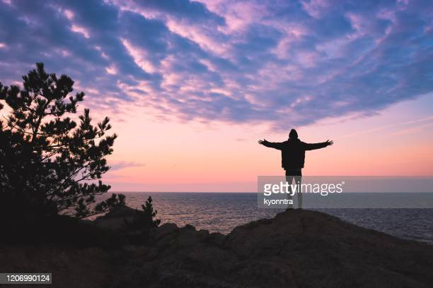 young man rise hand and refresh at the mountain - motivation stock pictures, royalty-free photos & images