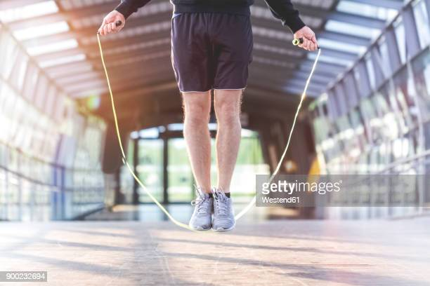 young man rope jumping on a bridge - skipping rope stock pictures, royalty-free photos & images