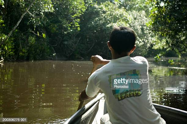 Young man rowing in wooden boat, rear view