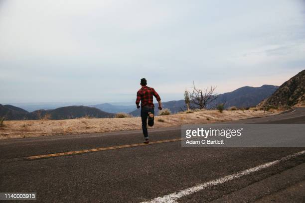 young man running across mountain road, los angeles, california, usa - escaping stock pictures, royalty-free photos & images