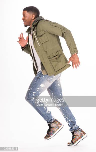 young man running against white background - casual clothing photos et images de collection