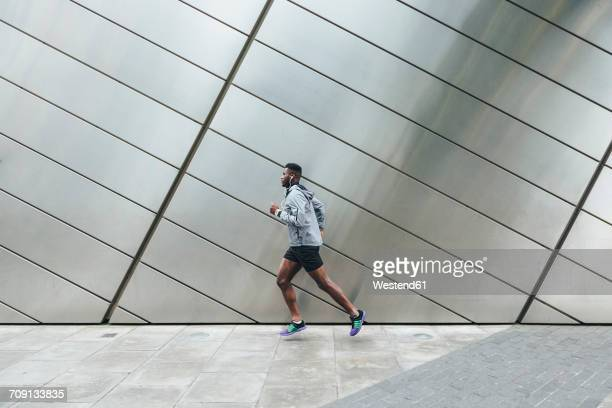 Young man running along building front