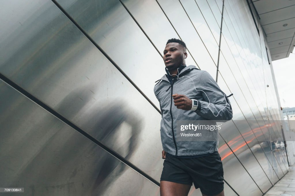 Young man running along building front : Foto de stock