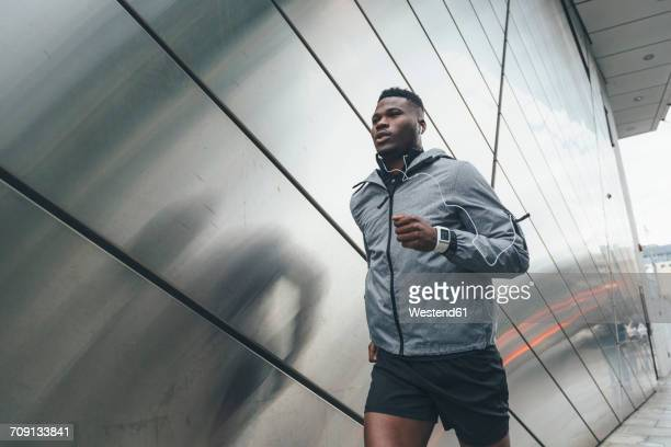 young man running along building front - black pants fotografías e imágenes de stock