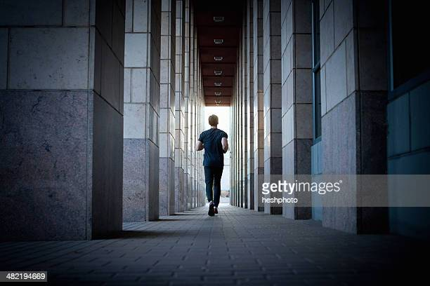 young man running along urban sidewalk - heshphoto stock pictures, royalty-free photos & images