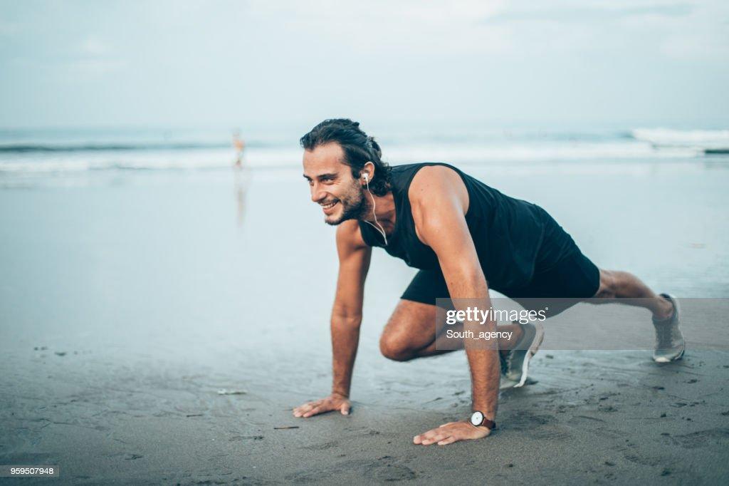 Junger Mann läuft am Strand : Stock-Foto