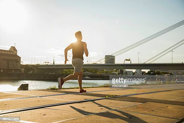 Young man running by the riverside